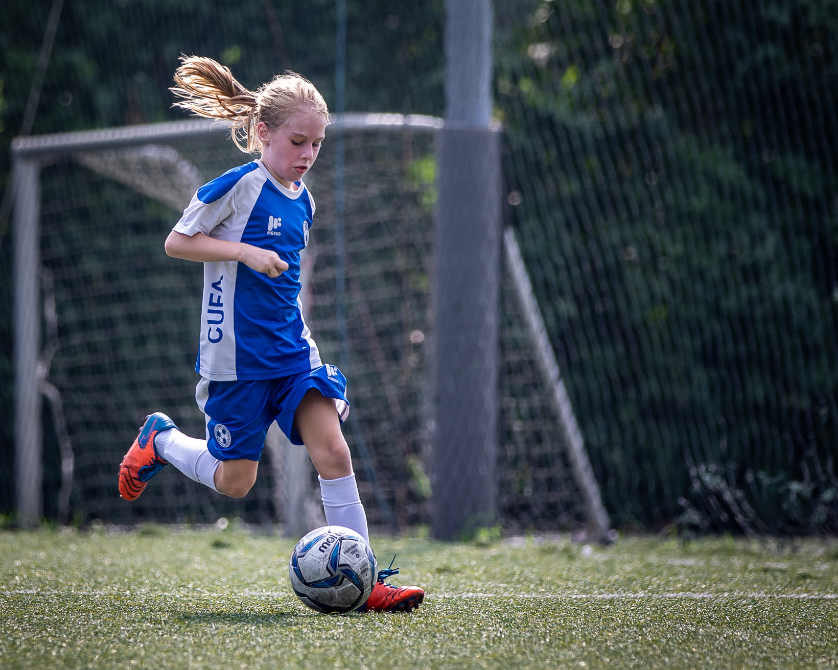 girl playing football on a football holiday camp